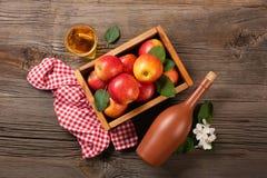 在木箱的成熟红色苹果有白花、玻璃和瓶分支的在一张木桌上的萍果汁 免版税库存图片