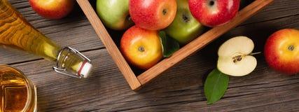 在木箱的成熟绿色和红色苹果有白花、玻璃和瓶分支的在一张木桌上的萍果汁 免版税图库摄影