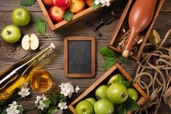 在木箱的成熟绿色和红色苹果有白花、玻璃和瓶分支的在一张木桌上的萍果汁 免版税库存照片