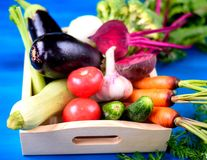 在木箱的新鲜蔬菜在蓝色木背景 库存照片