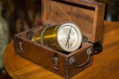 在木箱里面的古色古香的金黄指南针在表上 图库摄影