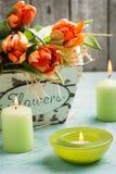 在木篮子和绿色的橙色郁金香点燃了cadles 库存照片