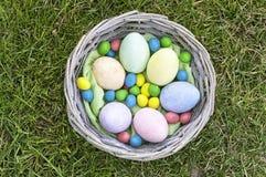 在木篮子的复活节彩蛋在草 免版税库存照片