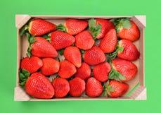 在木篮子的成熟甜草莓在绿色背景 免版税图库摄影