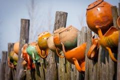 在木篱芭的泥罐 免版税库存照片