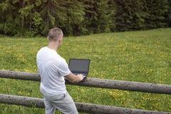 在木篱芭附近的人在一台膝上型计算机的身分在领域和工作在杉木森林附近 免版税库存照片