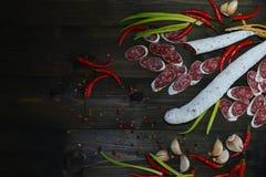 在木纹理书桌上的新鲜的fuet香肠用红辣椒、葱、大蒜和不同的类胡椒 图库摄影