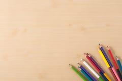 在木纹理桌上的颜色铅笔 免版税库存图片