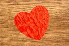 在木纹理特写镜头的被弄皱的纸心脏 免版税图库摄影