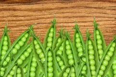 在木纹理特写镜头的绿色新鲜的豌豆 库存照片