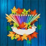 在木纹理的色的铅笔与秋叶 库存图片