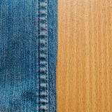 在木纹理的蓝色牛仔裤 免版税库存图片