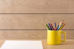 在木纹理的黄色杯子 库存照片