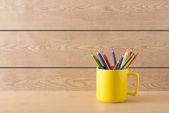 在木纹理的黄色杯子 库存图片