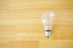 在木纹理背景的一个电灯泡 免版税库存照片