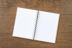 在木纹理背景的空白的白色笔记本 图库摄影