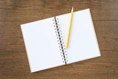 在木纹理背景的空白的白色笔记本 免版税库存照片