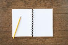 在木纹理背景的空白的白色笔记本 免版税库存图片