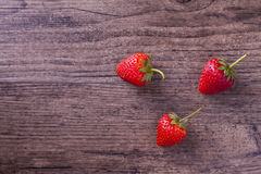 在木纹理背景的草莓 库存照片