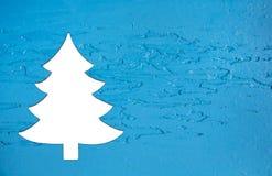 在木老蓝色背景的白色圣诞节树greetin的 库存图片