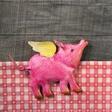 在木老被检查的背景的飞行的愉快的桃红色猪 免版税库存照片