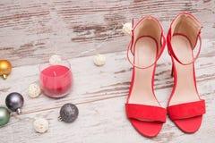 在木背景、毛皮树装饰品和蜡烛的红色绒面革鞋子 秀丽蓝色聪慧的概念表面方式构成妇女 免版税库存照片