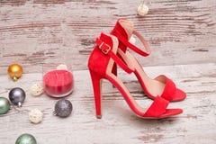 在木背景、毛皮树装饰品和蜡烛的红色绒面革鞋子 秀丽蓝色聪慧的概念表面方式构成妇女 库存照片