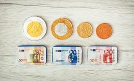 在木背景、钞票和硬币的巧克力金钱 免版税库存照片