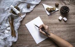 在木背景一只白色板料和手在黑铅笔写在纸和在左边蛋白软糖和甜点 免版税库存图片