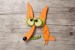 在木背景做的滑稽的菜狐狸 免版税图库摄影