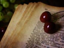 在木背景和樱桃莓果的减速火箭的书 免版税库存图片
