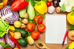 在木背景和笔记本的新鲜蔬菜 库存照片