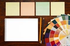 在木背景和笔记薄的色板显示指南 大模型 免版税图库摄影