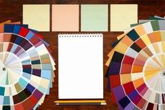 在木背景和笔记薄的色板显示指南 大模型 免版税库存照片