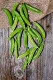 在木背景和黄麻袋子的新鲜的豌豆 库存图片