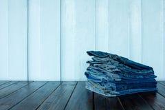 在木背景堆积的牛仔裤 免版税图库摄影
