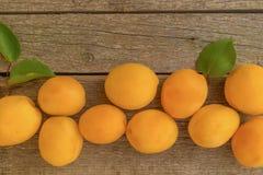 在木背景左侧的成熟橙色杏子 库存照片