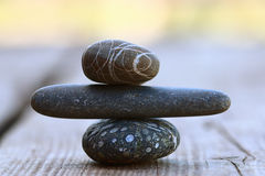 在木背景平衡概念的石头 库存照片