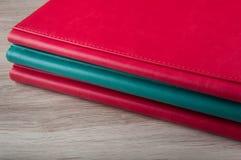 在木背景放置的三本皮革书 免版税库存图片