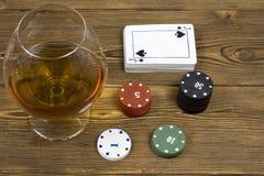在木背景是卡片组和一杯酒精,赌博 免版税库存图片