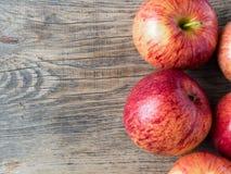 在木背景桌上的成熟水多的红色苹果 免版税库存图片