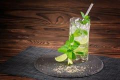 在木背景的一个刷新的mojito鸡尾酒 撒石灰mojito用兰姆酒、薄菏和苏打 酒精饮料玻璃 复制空间 免版税图库摄影