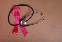 在木背景的一条桃红色丝带的特写镜头和听诊器, 库存图片