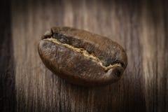 在木背景的一粒烤cofee豆 免版税图库摄影