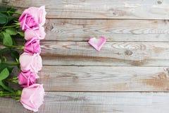 在木背景的七朵玫瑰 免版税库存照片
