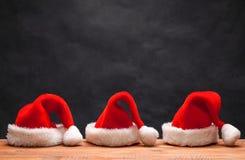 在木背景的三个圣诞老人红色帽子 免版税库存图片