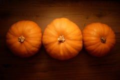 在木背景的三个橙色南瓜 免版税库存照片