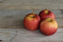 在木背景的三个苹果 免版税库存图片
