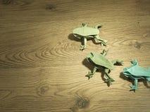 在木背景的三只Origami青蛙 免版税库存照片