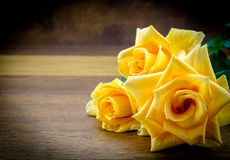在木背景的三朵黄色玫瑰 库存图片